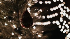 Woman decorating the red Christmas ball on a Christmas tree with bokeh lights background.  stock video