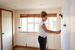 Woman Decorating Room In New Home Painting Wall stock photo