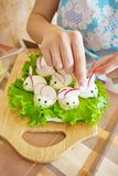 Woman is decorating stuffed eggs. Look like mouses Royalty Free Stock Photos