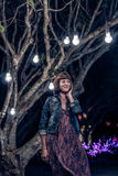 Woman among decorative outdoor string lights hanging on tree in the park at night time. Bali island, Indonesia. Royalty Free Stock Image