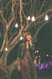 Woman among decorative outdoor string lights hanging on tree in the park at night time. Bali island, Indonesia. Stock Photos