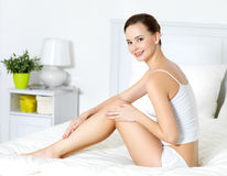 Woman in dedroom touching her beautiful legs Royalty Free Stock Images
