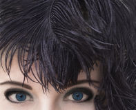 Woman with deep blue eyes in black feather headdress. Smoky eyes make-up. Stock Photography