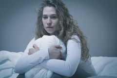 Woman with deep depression. Sitting in bed Royalty Free Stock Photos