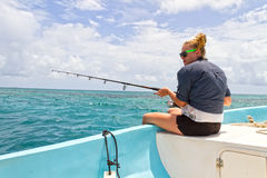 Woman deep sea fishing. From the side of a boat on the ocean under blue sky Stock Image