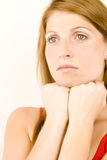 Woman deep in thought. A young woman deep in thought against a plain background Stock Photo