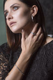 Woman Deep in Thought. Gold and Diamond Jewelry. A portrait close-up of an attractive adult woman who stopped deep in her thoughts, wearing a black dress Royalty Free Stock Images