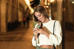 Woman with defocused urban city lights looking at her smartphone Stock Photos