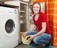 Woman  defrosting the refrigerator Royalty Free Stock Image