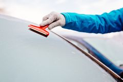 Woman deicing front car windshield with scraper Royalty Free Stock Photos