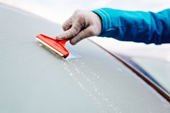 Woman deicing front car windshield with scraper Royalty Free Stock Images