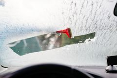 Woman deicing front car windshield with scraper Royalty Free Stock Photography