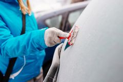 Woman deicing rear car windshield Royalty Free Stock Photos