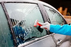 Woman deicing side car windshield with scraper Stock Photos