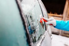 Woman deicing side car windshield with scraper Royalty Free Stock Images