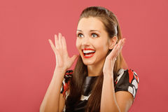 Woman delightfully plants hands. Young beautiful woman delightfully plants hands and is surprised, on red background Stock Image