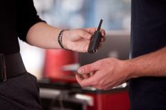 Woman Delivering Key to mechanic Stock Photos