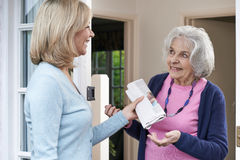 Woman Delivering Newspaper To Elderly Neighbour Royalty Free Stock Image
