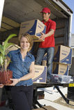 Woman With Delivery Man Unloading Moving Boxes From Truck Stock Photography
