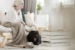Woman with dementia stroking dog Stock Image