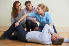 Woman Demonstrating Recovery Position In First Aid Training Clas Royalty Free Stock Photo