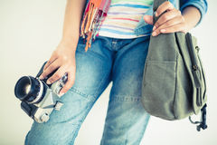 Woman in denim holding camera and shoulder bag Royalty Free Stock Photos