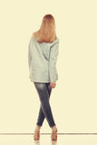 Woman in denim pants high gray shirt back view Royalty Free Stock Images