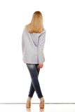 Woman in denim pants high gray shirt back view Stock Images