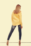 Woman in denim pants high yellow shirt back view Stock Photography
