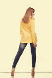 Woman in denim pants high yellow shirt back view Stock Image
