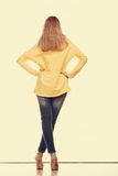 Woman in denim pants high yellow shirt back view Royalty Free Stock Photos