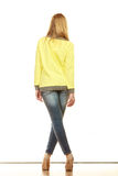 Woman in denim pants high yellow shirt back view Stock Photos