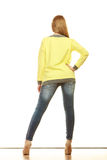Woman in denim pants high yellow shirt back view Royalty Free Stock Images