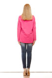 Woman in denim pants pink blouse back view Stock Photography