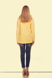 Woman in denim pants yellow blouse back view Royalty Free Stock Photo