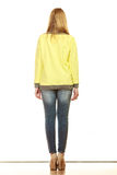 Woman in denim pants yellow blouse back view Stock Photo