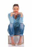 Woman in denim pose seated with hands on knees touching face Stock Photos
