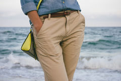 Woman in denim shirt and beige trousers walking along the beach Royalty Free Stock Image