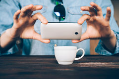 Woman in a denim shirt takes a picture of a cup of coffee at a c Stock Images