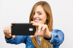 Woman in denim shirt taking self picture with phone Royalty Free Stock Photo