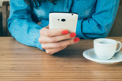 Woman in a denim shirt uses a smart phone in cafe Royalty Free Stock Images