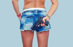 Woman in denim shorts is holding a gun behind her