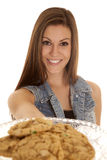 Woman denim vest hold out cookies Stock Photo
