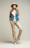 Woman in denim waistcoat and beige pants Stock Photography