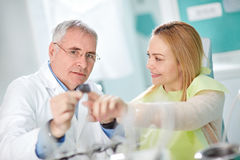 Woman in dental chair and dentist talk about her snapshot Stock Photo