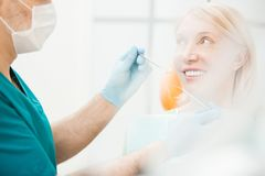 Woman in dental clinics. Smiling patient looking at her dentist in gloves and uniform before dental check-up Royalty Free Stock Image