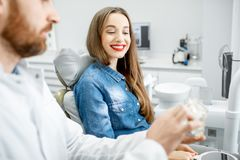 Woman during the dental consultation. Young beautiful women during the medical consultation with male dentist in the dental office stock images