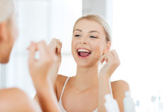 Woman with dental floss cleaning teeth at bathroom. Health care, dental hygiene, people and beauty concept - smiling young woman with floss cleaning teeth and Stock Image