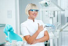 Woman dentist. Standing in her office with thumb up Royalty Free Stock Photography