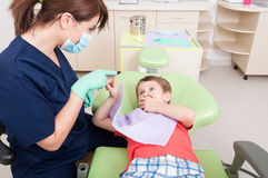 Woman dentist calming kid patient with games Stock Image